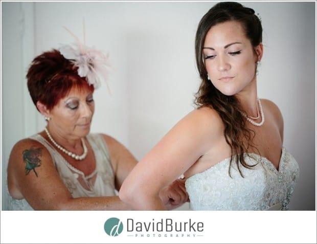 brides mother doing up back of dress