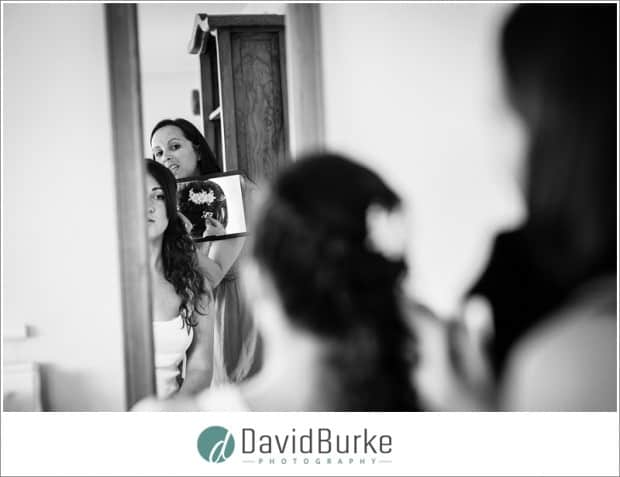 bride looking at hair in mirror