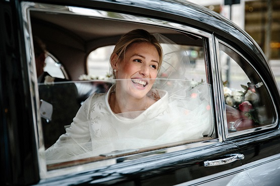 Happy bride in car at st clements dane church