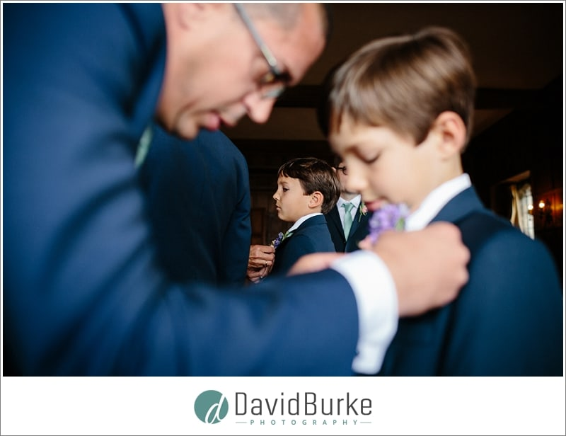 groom putting buttonhole on young best man