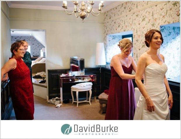 bridesmaid doing up dress