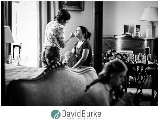 bride having makeup done in window light