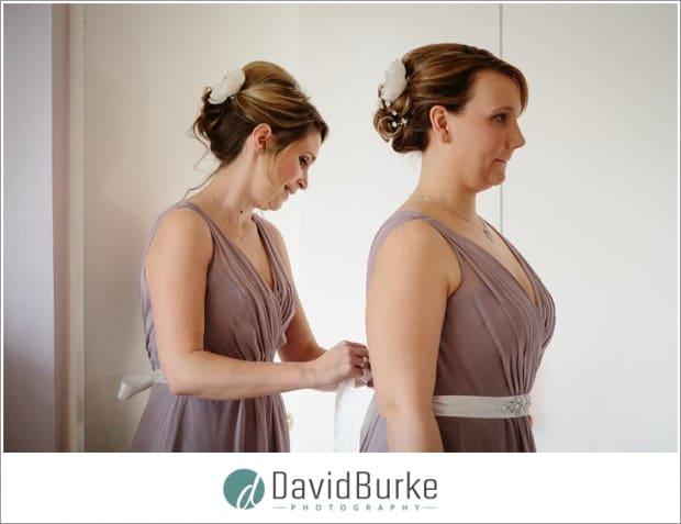 bridesmaids doing up dresses