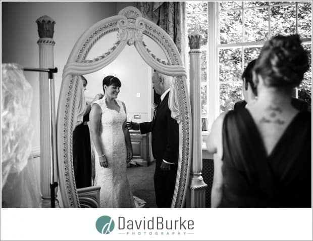 bride dressing in mirror with dad