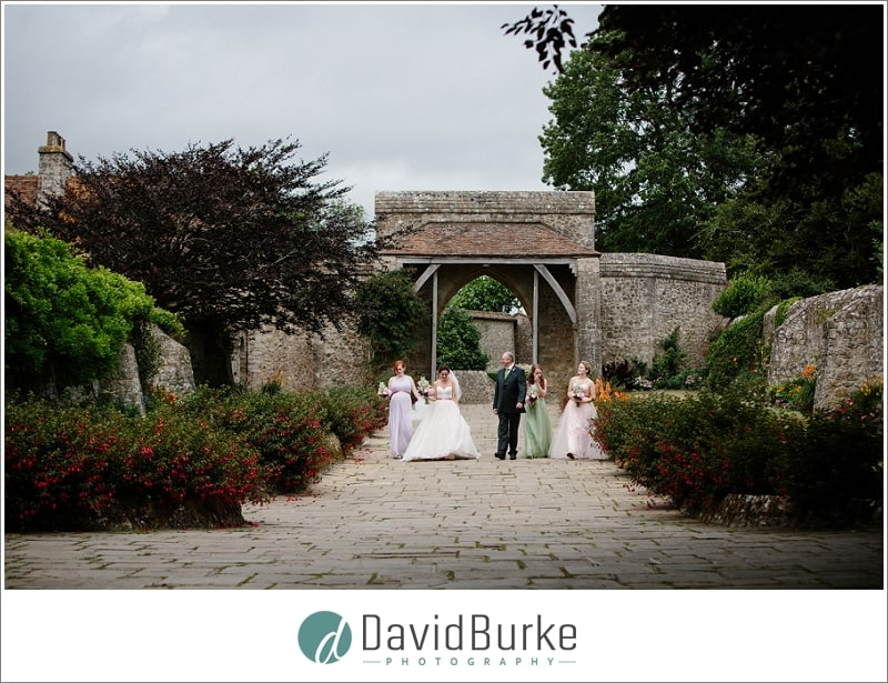 bridal party walk down lympne courtyard