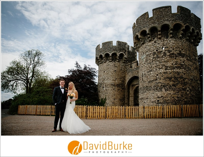 bride and groom in front of cooling castle barns